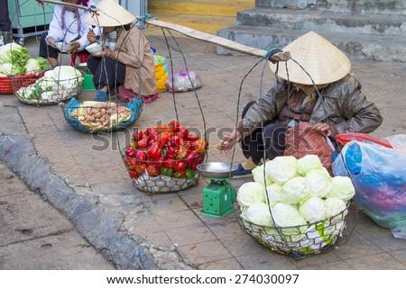 Vietnamese vendors selling fruit and vegetables at Dalat city market, Vietnam - stock photo