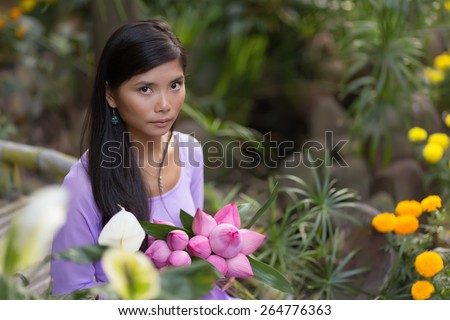 Vietnamese woman beauty holding lotus flower bud bunch - stock photo