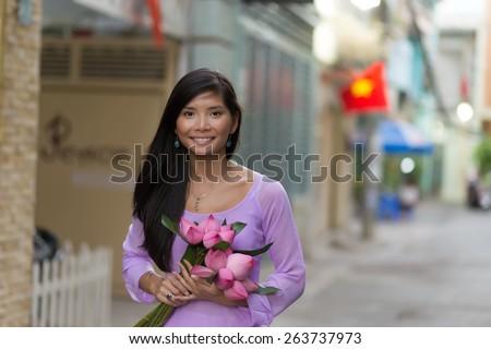 Vietnamese woman holding lotus flowers bud bunch - stock photo