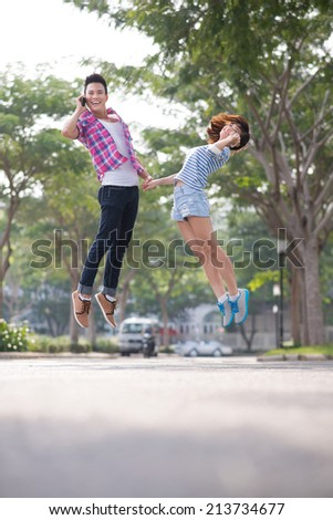 Vietnamese young couple jumping while talking on the phones - stock photo
