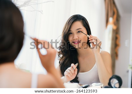 Vietnamese young girl applying mascara in front big mirror - stock photo