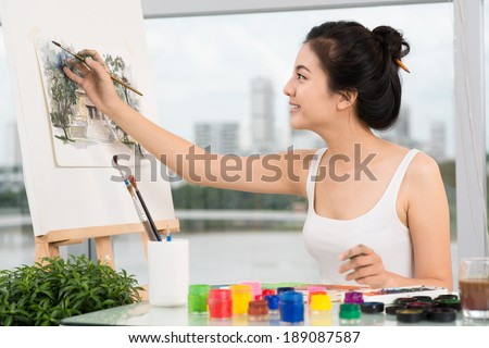 Vietnamese young lady painting a landscape - stock photo