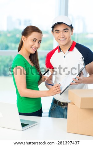 Vietnamese young woman signing document and paying with credit card for delivery - stock photo