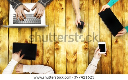 View above desk with peoples hands with gadgets - stock photo