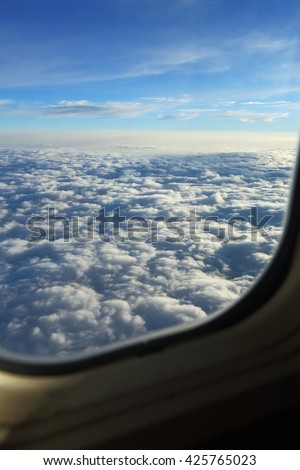 View above the clouds from an airplane window - stock photo