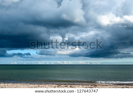 View across a deserted sandy beach of cumulonimbus storm clouds gathering over the ocean - stock photo