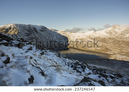 view across mountain lake in the snow, helvellyn cumbria - stock photo