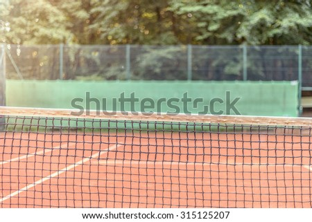 View across the length of the net on an all-weather tennis court towards side fencing with adverts, court is empty conceptual of sport, championships and tournaments - stock photo