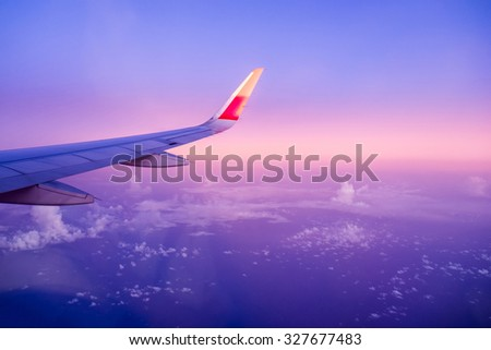 View airplane cloudy blue indigo sky twilight evening - stock photo