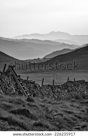 View along countryside fields towards misty Snowdonia mountain range in distance  black and white - stock photo