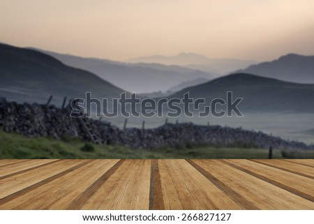 View along countryside fields towards misty Snowdonia mountain range in distance with wooden planks floor - stock photo