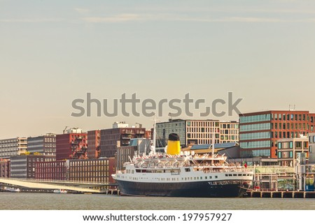 View at the Amsterdam KSNM island with a classic cruise liner in front - stock photo