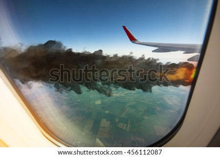 View at the flame of airplane engine from an illuminator. Traveler looking out the window on a falling airplane. (3D illustration) - stock photo