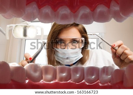 View at young female dentist with dental tools from patient's mouth  - stock photo