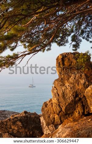 View catamaran sailing on the sea through the rocks Outdoors - stock photo