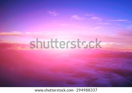 view colored clouds from an airplane at dawn - stock photo