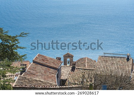 View down to the azure blue Mediterranean sea over the terracotta rooftops of Eze Village on a sunny day - stock photo