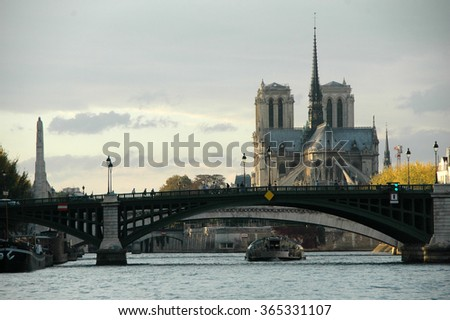 view from a boat on the Seine river near the Archbishop bridge with Notre Dame cathedral in the background in Paris during the evening - stock photo