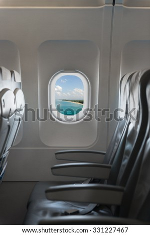 View from a commercial airplane cabin, blue sky and holiday destination, showing a row of comfortable chairs and armrests - stock photo