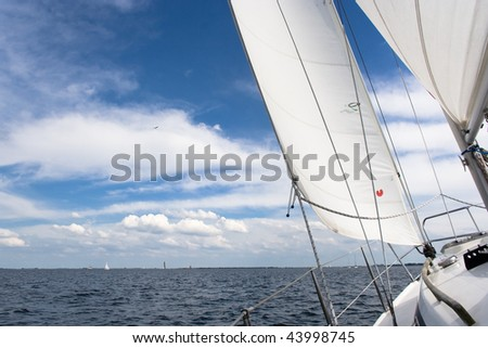 View from a sailing yacht, sailing in a nice breeze on a blue lake Grevelingen - stock photo