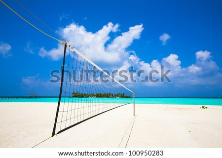 view from a volleyball net at the beach to a tropical island in the turquoise sea - stock photo