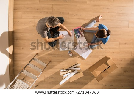 view from above, couple sitting on the floor of their new home on a sunny morning and reviewing blueprint to choose the decoration of their new interior. - stock photo