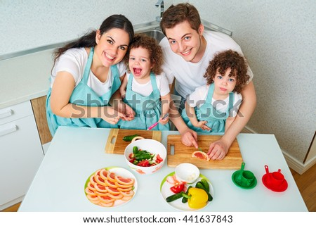 View from above. Daughters twins and parents in the kitchen cooking, smile and laugh, funny and happy. Portrait of young, happy family in the kitchen. A happy family. - stock photo