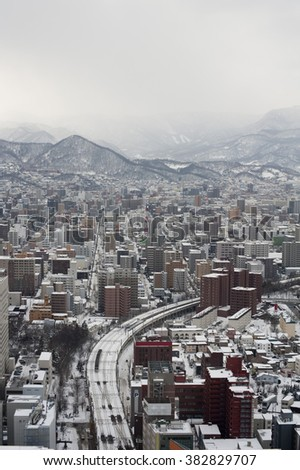 View from above down towards highway and buildings in Sapporo, Japan under overcast winter skies - stock photo