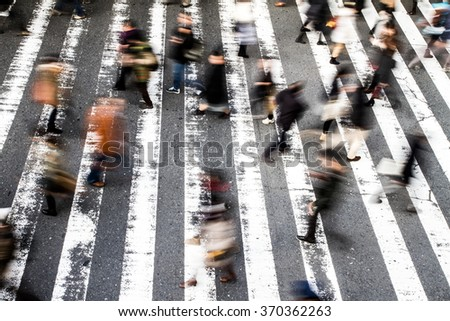 View from above of a crowd of pedestrians on a zebra crossing with motion blur to the walking people and focus to the stripes on the asphalt - stock photo