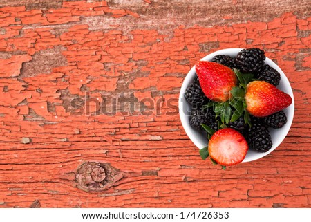 View from above of a small bowl of fresh ripe mixed berries containing strawberries and blackberries on a rustic grungy old wooden picnic table with peeling red paint and copy space for your text - stock photo