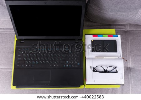 View from above of a tabletop workstation with open laptop, a diary, glasses and mobile phone are arranged in strict order on it - stock photo