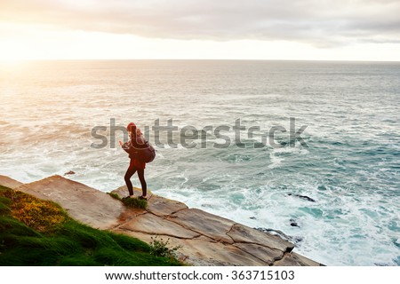 View from above of a woman reading text massage on cell telephone while standing against ocean background with copy space, female with trendy look watching video on mobile phone which she just shoots - stock photo