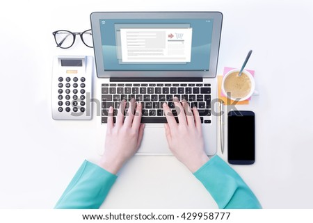 View from above of businesswoman sitting at desk and typing on laptop's keyboard while shopping online. Isolated on white background. - stock photo
