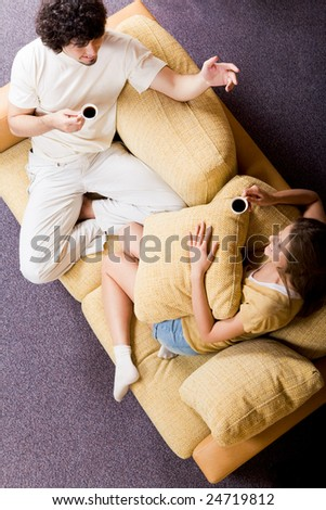 View from above of chatting couple sitting on sofa and drinking coffee in the morning - stock photo
