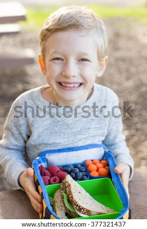 view from above of cheerful schoolboy eating healthy lunch during recess at school - stock photo