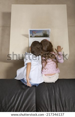 View from above of children looking at laptop computer - stock photo