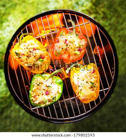 View from above of colorful red, green and yellow stuffed veggy savory bell peppers grilling on a BBQ with glowing hot coals - stock photo