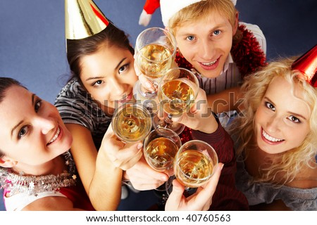View from above of flutes full of champagne being held by happy friends at birthday party - stock photo