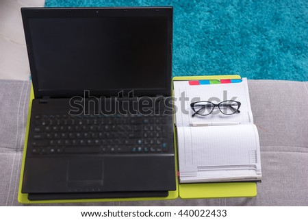 View from above of laptop-table with laptop, diary, glasses and pen, which are arranged in strict order  in living room - stock photo
