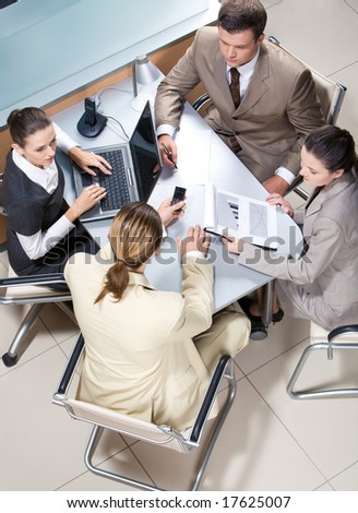 View from above of serious business group working at table in office - stock photo