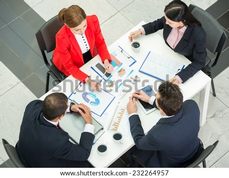 View from above of several business people are planning work around table. - stock photo