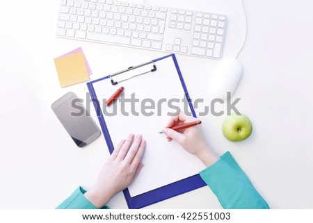 View from above of young businesswoman writing notes while sitting at office in front of computer.  - stock photo