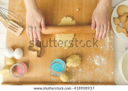 View from above of young woman rolling dough with wooden pin - stock photo
