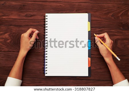 view from above on notepad and pencil in womans hand - stock photo