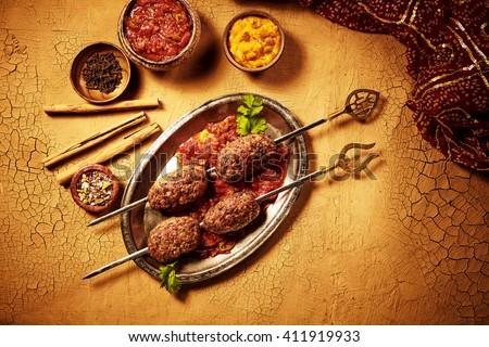 View from above on shish kebab meat Indian meal in metal plate with sauces and spices with dried bamboo sticks on cracked paint surface - stock photo