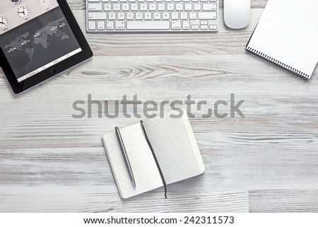 View from above on the clean, well organized working space at the office with tablet, keyboard, computer mouse, notepad. - stock photo