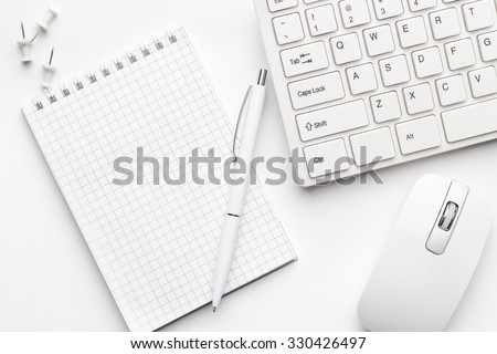 view from above on white office table with notepad and computer - stock photo