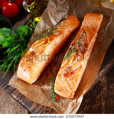 View from above or two succulent grilled salmon steaks seasoned with herbs on crumpled brown paper in a rustic kitchen with herbs, tomatoes and olive oil - stock photo