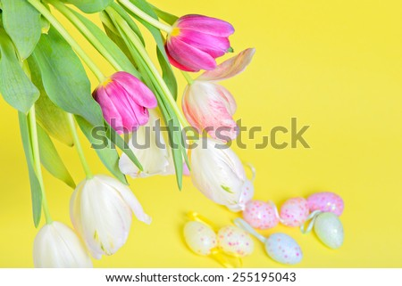 View from above to the easter multicolored tulips and eggs over yellow paper - stock photo