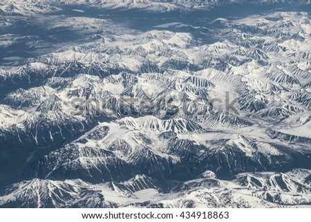 View from airplane on Earth surface - snow-capped mountains. - stock photo